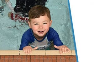 young boy smiling in children's pool